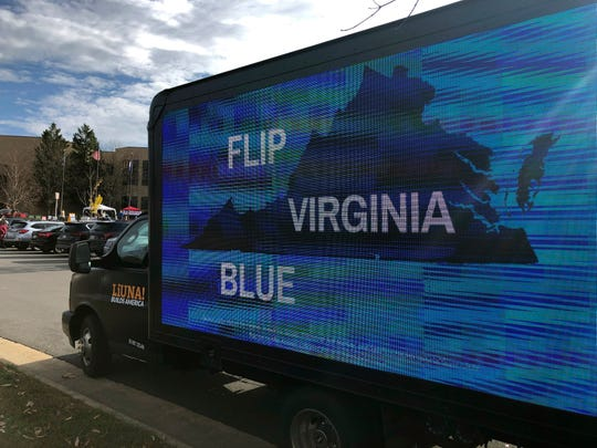 A mobile billboard urges voters to cast ballots for Democrats outside Centreville High School in Clifton, Va., Tuesday, Nov. 5, 2019.