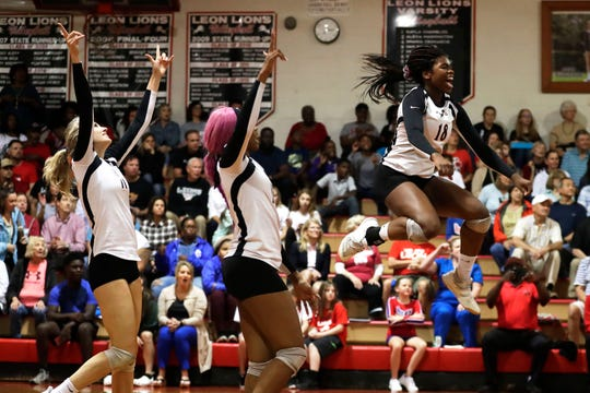 Leon's Cailin Demps (18) celebrates a point with Macy Maxwell and A'Nylah Cobb as the Lions swept Buchholz in three sets to win the Region 1-6A final on Tuesday, Nov. 5, 2019.