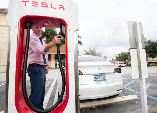 """""""This is an affordable, very convenient car,"""" said Evan Berry, of Port St. Lucie, who charges his Tesla Model 3 on Wednesday, Oct. 23, 2019, at a Tesla charging station in Port St. Lucie. Berry says the electric vehicle has added $20-$30 on his home electric bill, which he considers a savings from the $300 he used to spend on gas monthly."""