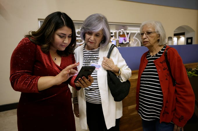 Cassandra Hernandez checks voting numbers on her phone during her election night party Tuesday.