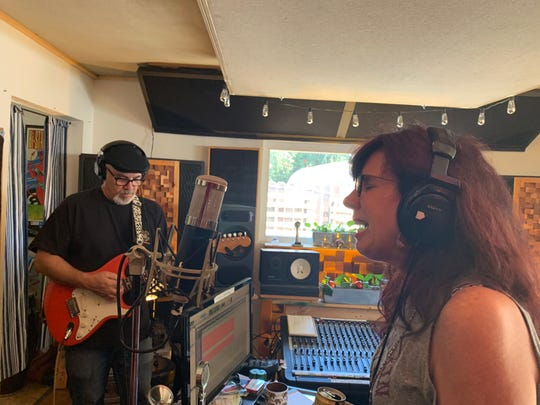Mary Fishell Sawyer, of the Vonettes, sings while Mike Fishell plays on guitar during their recording for nonprofit Totally Local VC's Local Love CD project. Sales of the CD will go to help the victims of the Thomas Fire.