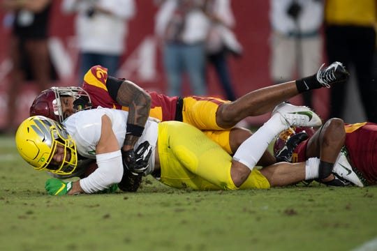 Calabasas High graduate Mycah Pittman is tackled by USC safety Isaiah Pola-Mao during Oregon's win on Saturday.