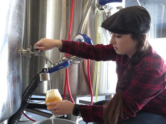 Tayler Tomei, general manager at Tarantula Hill Brewing Co. in Thousand Oaks, taps a glass of its 4-SAM-3 Helus Golden Ale directly from the tank. The beer named for fallen Ventura County Sheriff's Sgt. Ron Helus will be released to the public on Nov. 11.