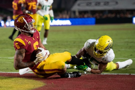 Oaks Christian School graduate Michael Pittman Jr., left, hauls in a touchdown pass after beating Oregon safety Nick Pickett during USC's home loss on Saturday night.