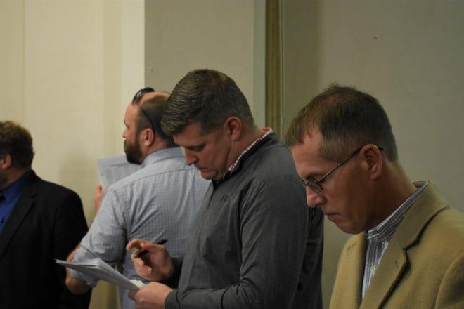 Matt Abbott (center) and Bill Arnett (right) check their notes during the auditor's sale Wednesday. Abbott was bidding on behalf of the port authority, while Arnett was bidding on behalf of the CIC.