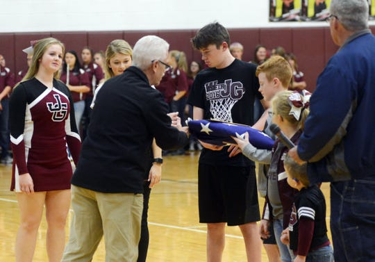 U.S. Representative Bill Johnson gives the American flag, which honored John Glenn, to Bob Applegate (right) and his grandchildren (from left), Bexlee, Wylee and Dayzee Woodard and Knox Watson, during a ceremony at John Glenn High School. The grandchildren gifted the flag to the high school as John Glenn students Taylor Zemba (far left) and Felicity Boykin accepted it.