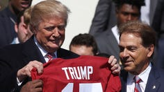 WASHINGTON, DC - APRIL 10: U.S. President Donald Trump stands with coach Nick Saban (R), while presented with a team jersey while honoring the 2017 NCAA Football National Champion Alabama Crimson Tide during an event at the White House, on April 10, 2018 in Washington, DC. Alabama beat the Clemson Tigers 35-31 to capture the championship.  (Photo by Mark Wilson/Getty Images) ORG XMIT: 775151098 ORIG FILE ID: 944388946