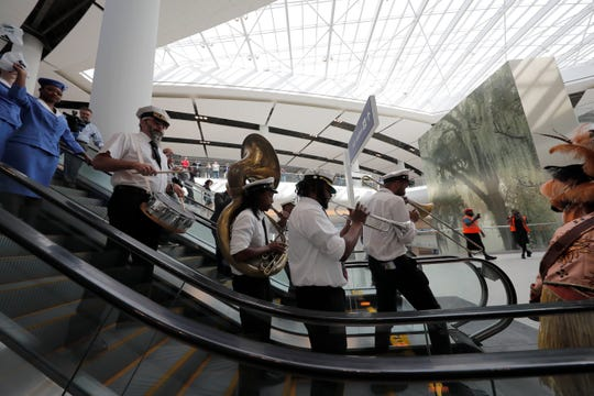 A brass band leads a parade down escalators during festivities for the opening of the newly built main terminal of the Louis Armstrong New Orleans International Airport.