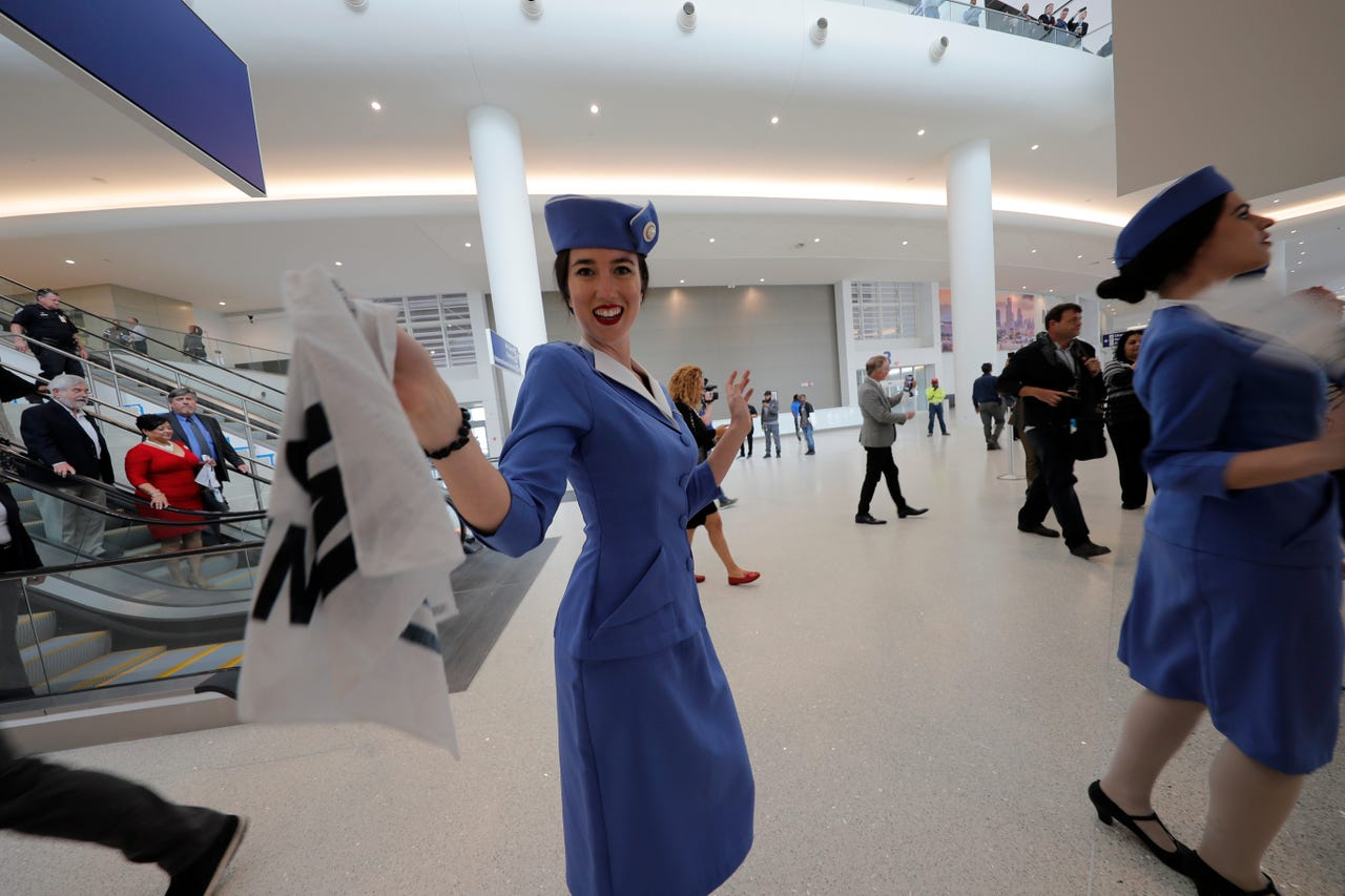Women dressed as flight attendants dance and wave handkerchiefs to a second line parade during festivities for the opening of the newly built main terminal of the Louis Armstrong New Orleans International Airport in Kenner, Louisiana, Tuesday, Nov. 5, 2019.