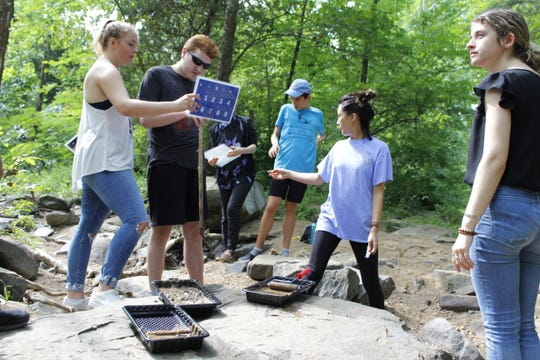 Ian Nordling, 21, spells with intern Ashley Sullender, 19, while mixing mud for eco-graffiti.
