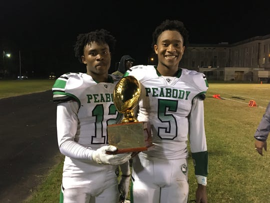 Peabody's Thomas (left) and Tyriq Miles hold the Blue-Green Classic Trophy after defeating Bolton 20-6 Nov. 1. The brothers have played a big role in the Warhorses' 6-3 start as quarterback and receiver.