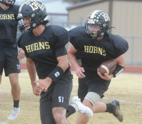 Gordon quarterback Brandon Mahan (13) leads the way for running back Hoss Rouse during practice Wednesday at Longhorn Stadium.