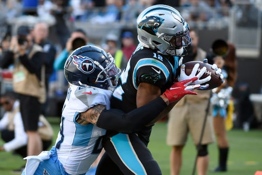 Tennessee Titans strong safety Kenny Vaccaro, left, tackles Carolina Panthers wide receiver D.J. Moore (12) after a catch during the second half in Charlotte, N.C., Sunday, Nov. 3, 2019.
