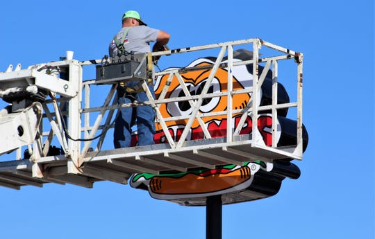 A worker gets eyed as he finishes work this week on the Grump Burgers restaurant sign on North First Street. The location is due to open in December.