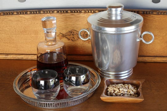 Glassware in the style of Dorothy Thorpe, a mid-century designer of glasses, grace a buffet. The ice bucket and nut bowl are both vintage, while the decanter is new, purchased from World Market.