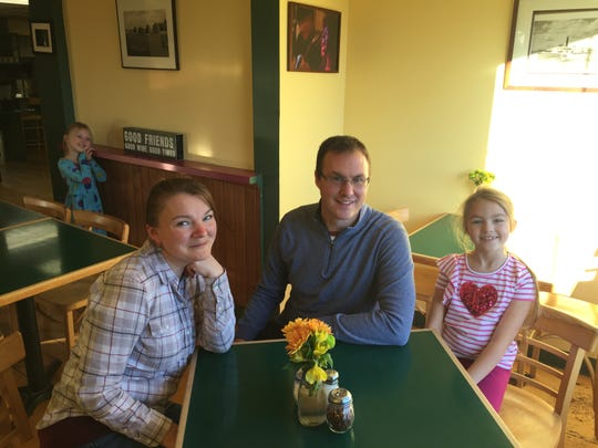 Good Times Cafe owners Maryam and Travis Counter sit with their daughter, Liliya, 8, while daughter Zoya, 6, stands in the background at the Hinesburg restaurant on Nov. 6, 2019.