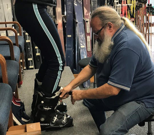 Boot-fitter Bill Caden serves a customer at the newly re-opened Danzeisen & Quigley in Cherry Hill.