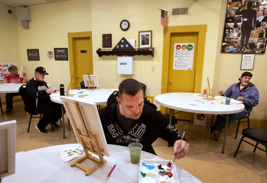 Joey Daniel, 34, U.S. Army, 2005-2013, center, takes part in an art class at Joseph House.