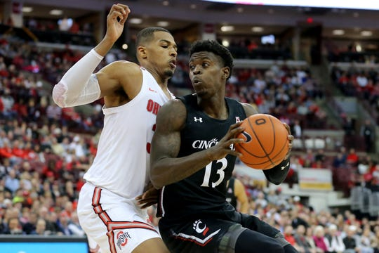 Cincinnati Bearcats forward Tre Scott (13) spins toward the basket as Ohio State Buckeyes forward Kaleb Wesson (34) defends in the second half of a college basketball game, Wednesday, Nov. 6, 2019, at Value City Arena in Columbus, Ohio. The Ohio State Buckeyes won 64-56.