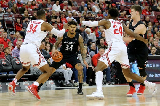 Cincinnati Bearcats guard Jarron Cumberland (34) dribbles between the two Wesson brothers of Ohio State, Kaleb (34) and Andre ( 24) in the second half of a college basketball game Wednesday, at Value City Arena in Columbus. The Buckeyes won 64-56.