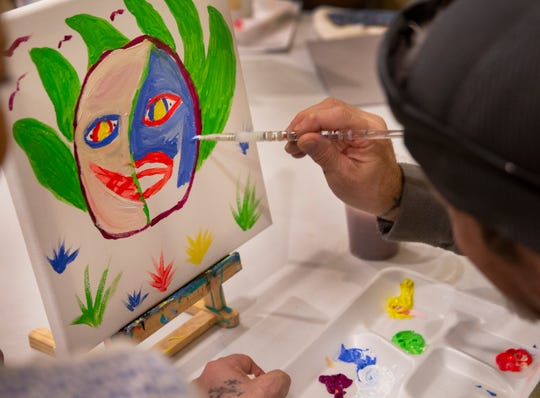Harry Kavadas, 59, U.S. Army veteran, works on his split face painting during art class at Joseph House in Over-the-Rhine.