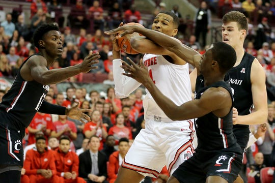 Ohio State's Kaleb Wesson pulls down a rebound between Cincinnati's Tre Scott (13) and Keith Williams (2) during the first half of Wednesday's game in the Schotenstein Center. Ohio State won 64-56.