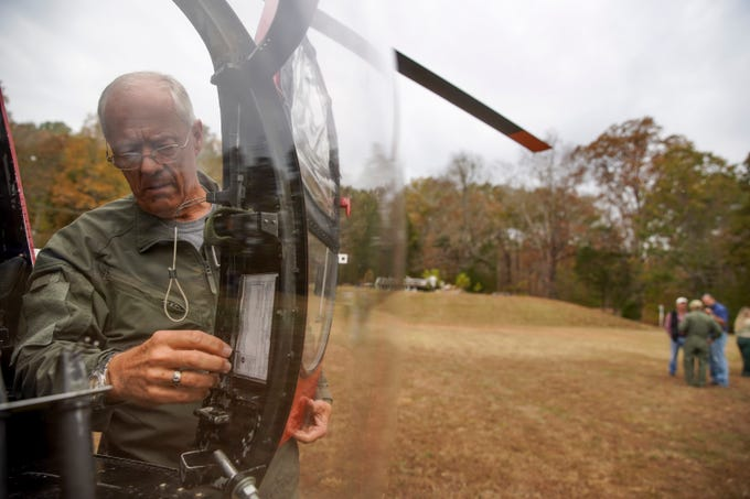 A pilot with the USDA Wildlife Services attaches doors to the small helicopter that will be used for controlling feral pig populations at Brandon Spring in Land Between the Lakes, Tenn., on Wednesday, Nov. 6, 2019.