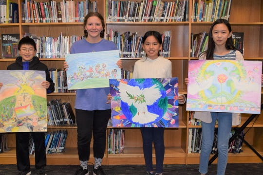 Darren Xu, grade 6, Catherine Ryder, grade 7;  Kayla Peng and Clara Risso, grade 6 are photographed holding their submissions for the Journey of Peace contest.