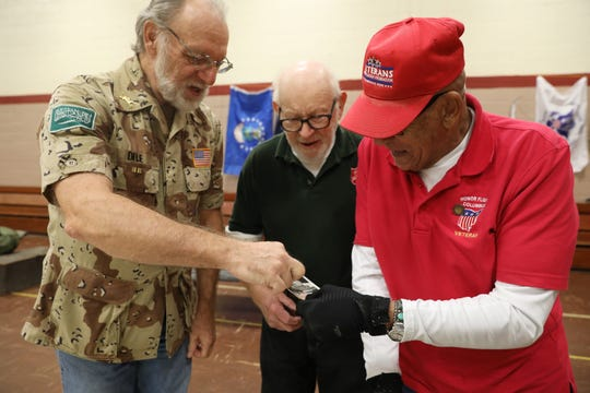 Tom Dile, left, talks about a picture with fellow Army veteran Maurice Sheffield during the Salvation Army's Veterans Day event. With them is Willis Pigman of the Salvation Army.