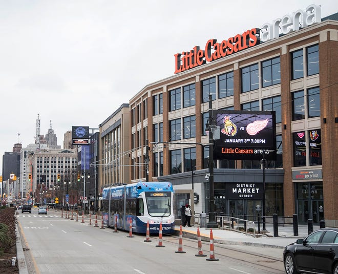 A QLine streetcar goes by in front of the Little Caesars Arena in Detroit, Thursday, December 21, 2017.