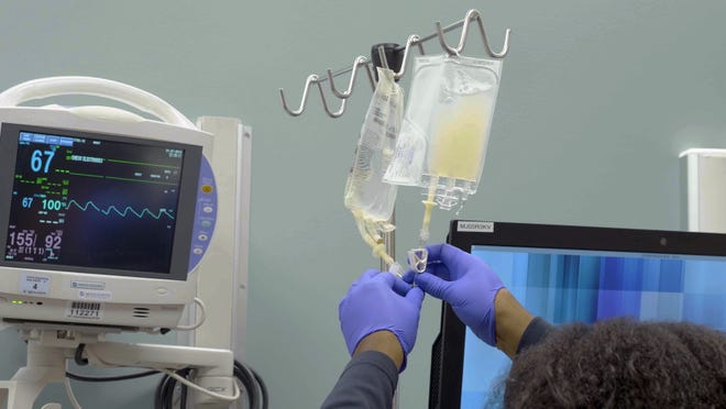 In this January 2019 image made from video provided by Penn Medicine, IV bags of CRISPR-edited T cells are prepared for administering to a patient at the Abramson Cancer Center in Philadelphia.