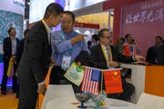 In this photo taken Wednesday, Nov. 6, 2019, visitors chat near American and Chinese flags displayed at a booth of an American company during the China International Import Expo in Shanghai. Washington and Beijing have agreed to cancel tariff hikes as their trade negotiations progress, a Chinese Commerce Ministry spokesman said Thursday, Nov. 7, 2019.