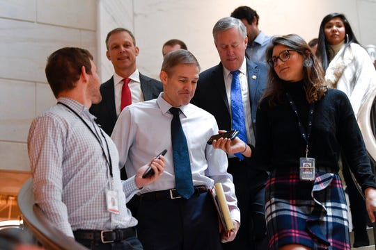 Rep. Jim Jordan, R-Ohio, center, Rep. Scott Perry, R-Pa., second from left, and Rep. Mark Meadows, R-N.C., fourth from left, are surrounded by reporters on Capitol Hill in Washington, Thursday, Nov. 7, 2019.