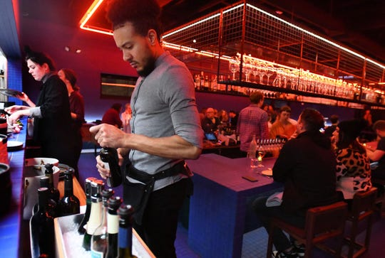 Server Thor Jones opens a bottle of wine for a customer at Magnet, a new restaurant that has done away with the tipping model in Detroit, Michigan on November 6, 2019.