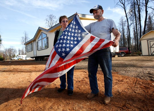 Joyce and Jerry McLean unfurl an American flag outside their new modular home that was recently moved in to replace their home that was destroyed by last year's Camp Fire, in Paradise, Calif., Tuesday, Nov. 5, 2019.