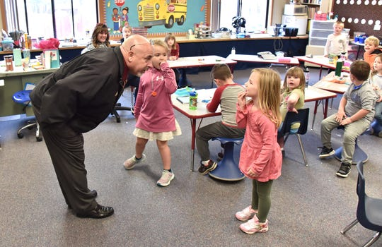 Leia Mullins, 5, shows DeTour Area Schools Superintendent/Principal Robert Vaught her missing front teeth last week as Lillian LaKies, 5, watches in Amy Moser's kindergarten class on Drummond Island.