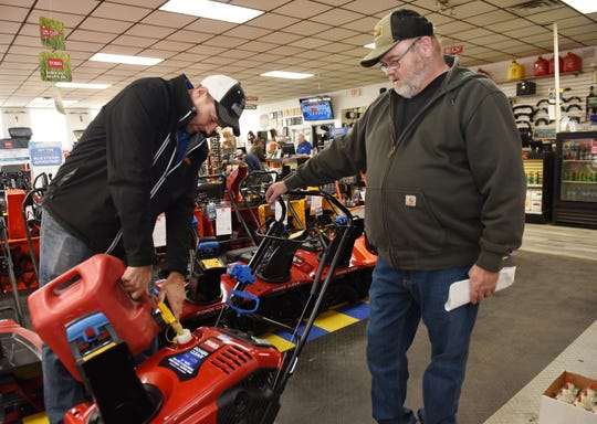 Dave Hellebuyck, 40, (l), General Manager at Hellebuyck's, he is seen pouring gas into John Williams, 62, of Roseville's new snow blower that he just purchase at the center.