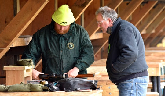 MI DNR Range Officer Josiah Clemence, left, helps Marc Robichaud, of West Bloomfield, before he shoots in his Remington 30-06 on the 50 yard range.