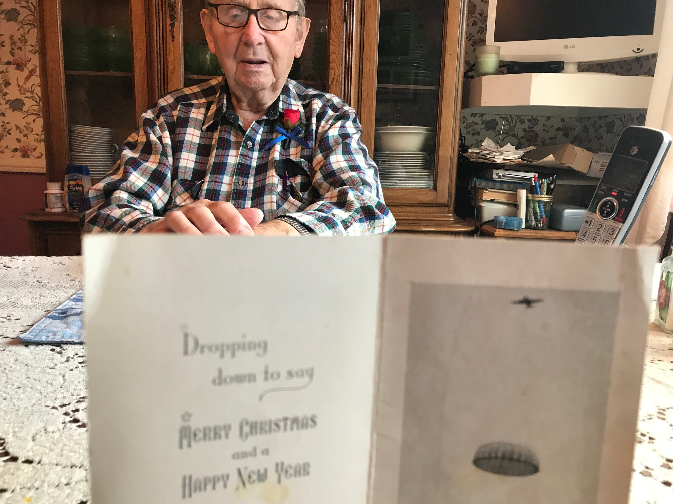 Calvin Haar, 95, talks about his experiences during World War II as a U.S. Army paratrooper. In the foreground is a holiday card he sent to his wife, Betty, from Europe during the war.