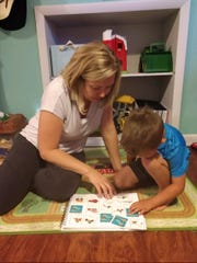 Katee Guderjahn and her son Brady play a game from the Vroom app.