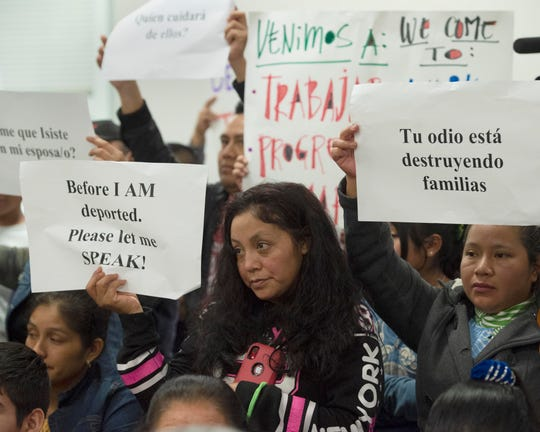 Attendees of a meeting of the Committee on Homeland Security hold up signs in demonstration on Thursday, Nov. 7, 2019 at Tougaloo College in Jackson, Miss. following ICE raids in Mississippi in August that detained nearly 700 persons.