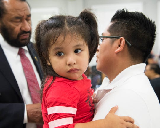 Fredy Salvador holds his 2-year-old daughter Judy while speaking with U.S. Congressman Al Green of Texas following a public Field Hearing held by the Committee on Homeland Security on Thursday, Nov. 7, 2019 at Tougaloo College in Jackson, Miss. Mr. Salvador's wife, an employee of Koch Foods at the time of the ICE raids in August, was detained and released by ICE, but will return to court for an immigration hearing next week. The event at Tougaloo on Thursday was held to address the impact of mass ICE raids conducted in Mississippi.