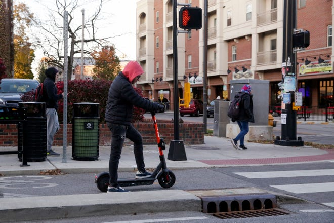 A Spin scooter rider stops at the intersection of State and Pierce Streets, Thursday, Nov. 7, 2019, in West Lafayette.
