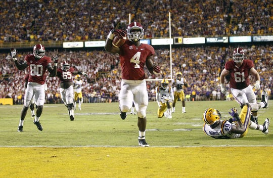 Alabama running back T.J. Yeldon (4) scores against the LSU Tigers at Tiger Stadium on Nov. 3, 2012. Tigers cornerback Jalen Mills (28) took the blame due to a foiled blitz.