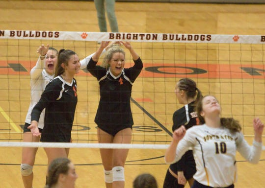 From left, Brighton's Evelynn Lemons, Celia Cullen and Ashley Brown celebrate a district semifinal volleyball victory over South Lyon on Wednesday, Nov. 6, 2019.