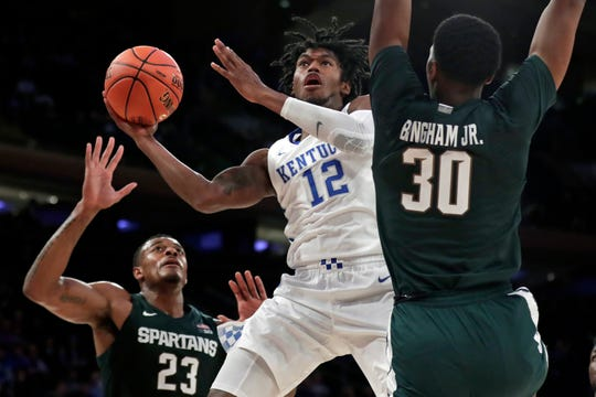 Kentucky forward Keion Brooks (12) drives to the basket between Michigan State forwards Marcus Bingham Jr. (30) and Xavier Tillman (23) during the second half of an NCAA college basketball game Tuesday, Nov. 5, 2019, in New York. Kentucky won 69-62. (AP Photo/Adam Hunger)