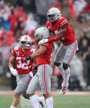 Ohio State safety Jordan Fuller congratulates defensive end Chase Young after one of his four sacks in the 38-7 win over Wisconsin. Young is sitting out Saturday's Maryland game because of a potential problem with his NCAA status.