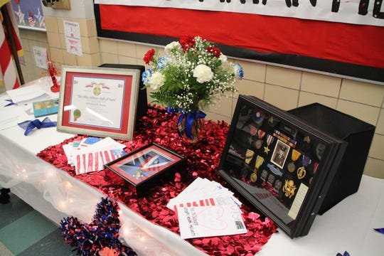 """This display includes Sgt. David S. """"Dave"""" Harris' medal and certificate from the Ohio Military Hall of Fame as well as other military memorabilia and thank you letters from Pleasant Middle School students to veterans."""