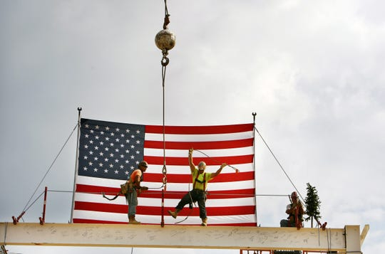 Workers put the final steel in place during the August 2012, topping out ceremony at the new $200 million Mitsubishi Electric plant under construction at Rivergate Industrial Park.