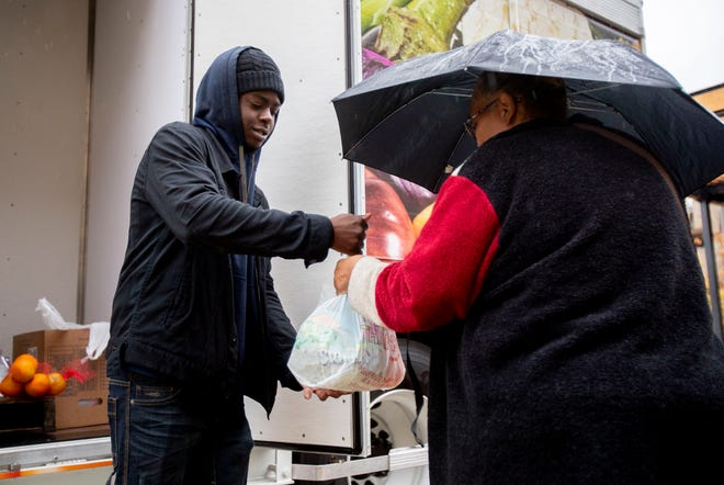 Mid-South Food Bank employee Ramico Brown, left, hands Sadie Hurd a bag of produce Thursday, Nov. 7, 2019, outside Crosstown Concourse in Memphis.